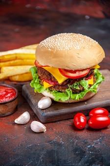Мясной бургер, вид спереди, сырный салат и помидоры на темном полу