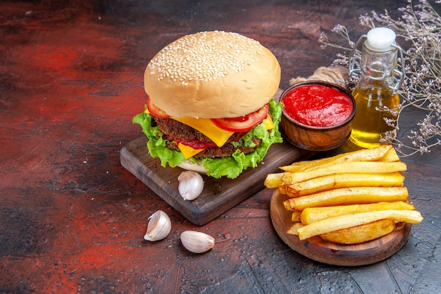 Front view meat burger with cheese salad and tomatoes on a dark background