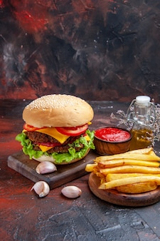 Front view meat burger with cheese salad and tomatoes on the dark background