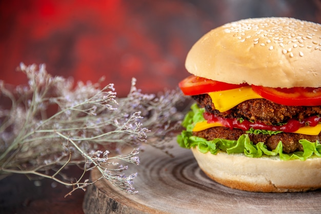 Front view meat burger with cheese tomatoes and salad on dark background