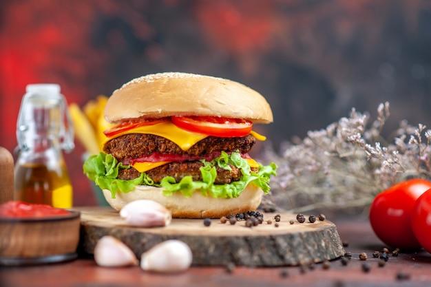Hamburger di carne vista frontale con patatine fritte su sfondo scuro