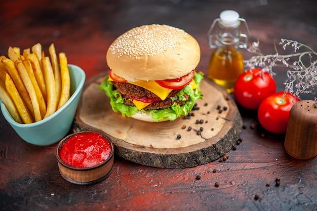 Мясной бургер, вид спереди с картофелем фри на темном столе