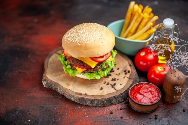 Вид спереди мясной бургер с картофелем фри на темном фоне