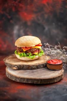 Мясной бургер с салатом, сыром и помидорами на темном столе, фаст-фуд, сэндвич с булочкой, вид спереди