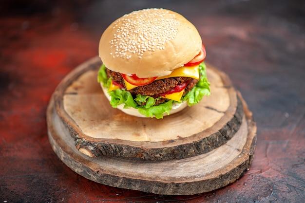 Мясной бургер, вид спереди, салат, сыр и помидоры на темном полу, бутерброд с булочкой, фаст-фуд