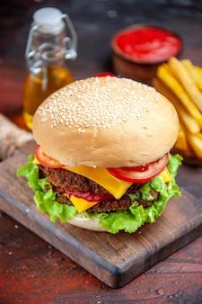 Вид спереди мясной бургер с помидорами, сыром и салатом на темном фоне
