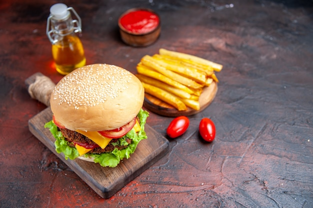 Мясной бургер с помидорами, сыром и салатом, вид спереди на темном столе