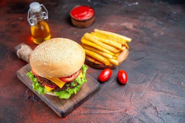 Hamburger di carne di vista frontale con pomodoro, formaggio e insalata sulla scrivania scura