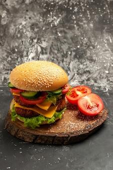 暗い表面のサンドイッチパンファーストフードに野菜とチーズを添えた正面図のミートバーガー