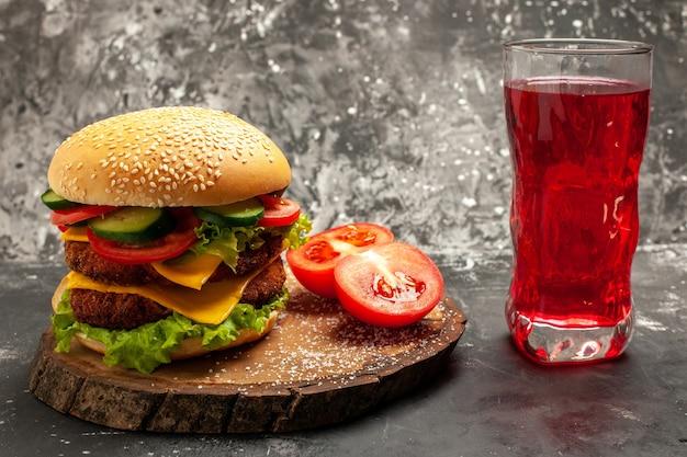 暗い表面のサンドイッチファーストフードパンに野菜とチーズを添えた正面のミートバーガー