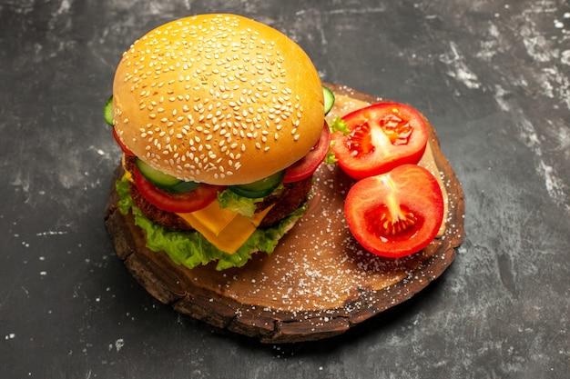 暗い表面のパンファーストフードサンドイッチに野菜と正面のミートバーガー