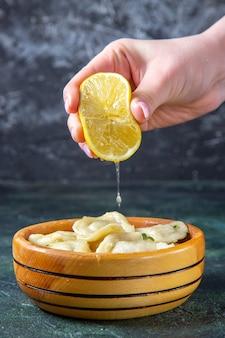 Gnocchi di carne vista frontale con spremitura di succo di limone da femmina su superficie blu scuro