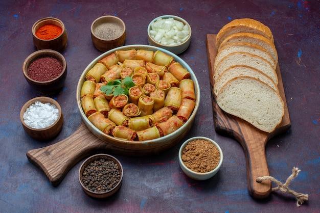 Vista frontale involtini di carne arrotolati in zucche insieme a condimenti e pane sul pasto cena cibo vegetale di carne superficie scura