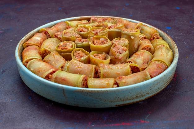 暗い表面の鍋の中で野菜と一緒に巻かれた正面の肉ロール肉夕食食品食事野菜