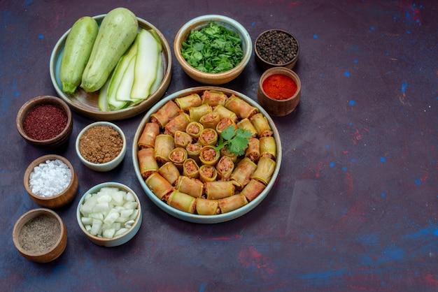 正面図肉ロールは、暗い机の上に緑と調味料を入れた鍋の中に野菜を巻いた肉ディナー食品野菜料理