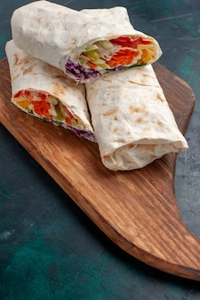 正面図の肉サンドイッチ灰色の机の上に野菜と唾を吐きながら焼き肉で作ったサンドイッチ