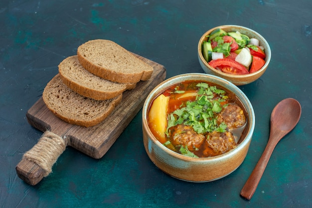 Front view meat soup with meatballs greens and sliced potatoes with bread loafs on dark blue desk food soup sauce vegetable dish