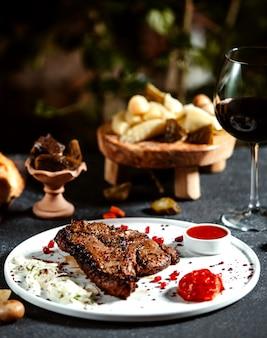 Вид спереди мясной стейк на тарелке с луковым кетчупом и бокалом красного вина