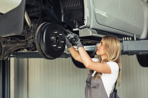 Front view mechanic female fixing car