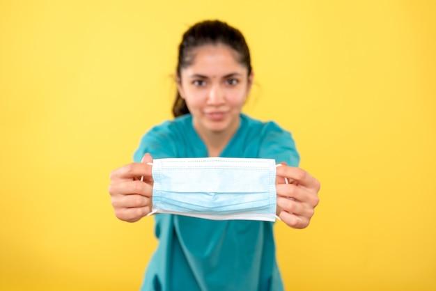 Vista frontale della mascherina medica in mano femminile sulla parete isolata gialla