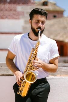 Вид спереди среднего музыканта, играющего на саксофоне