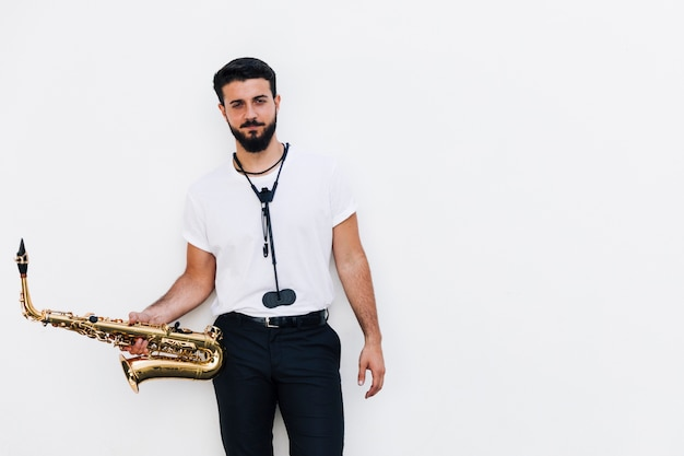 Front view medium shot musician posing with saxophone