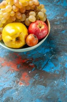 正面図まろやかな果物マルメロリンゴとブドウの内側のプレートの青い背景健康ダイエットビタミン熟した写真おいしい