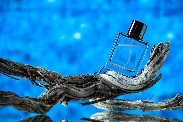 Bottiglia di colonia da uomo vista frontale sul ramo di un albero marcio su sfondo blu
