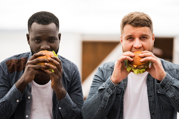 Front view men eating burgers together
