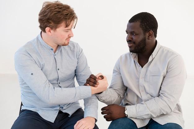 正面の男性が手を繋いでいるとお互いを慰める