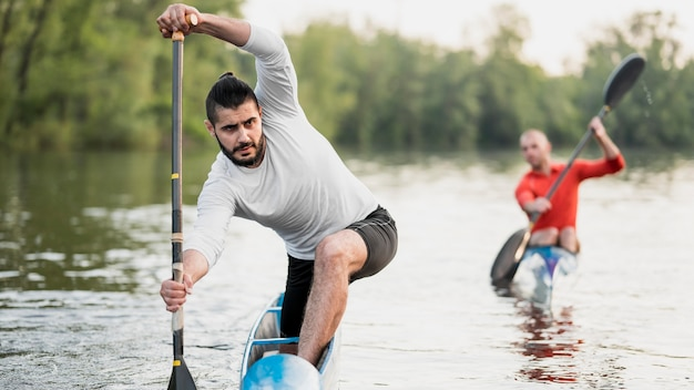 Front view men holding oars