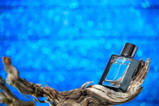 Вид спереди мужские духи на ветке гнилого дерева на синем фоне