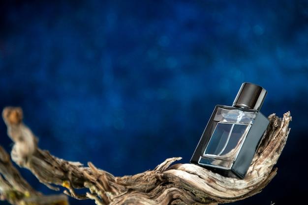 Вид спереди мужские духи на ветке гнилого дерева на темно-синем фоне