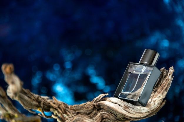 Вид спереди мужские духи на высушенной ветке дерева, изолированные на темно-синем фоне, свободное пространство