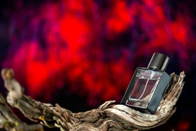 Вид спереди мужские духи на высушенной ветке дерева, изолированные на темно-красном фоне, свободное пространство