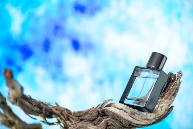Вид спереди мужские духи на высушенной ветке дерева, изолированные на голубом фоне, свободное пространство