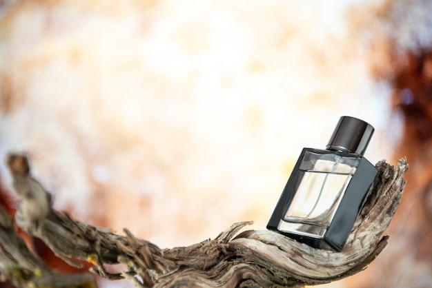 Вид спереди мужские духи на высушенной ветке дерева, изолированной на обнаженном фоне, свободное пространство