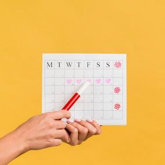 心と花を持つフロントビュー月経カレンダー