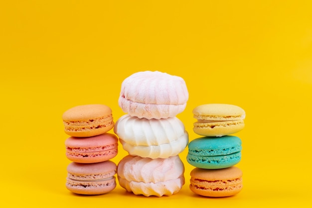 A front view meringues and macarons delicious and baked cakes isolated on yellow, cake biscuit confiture