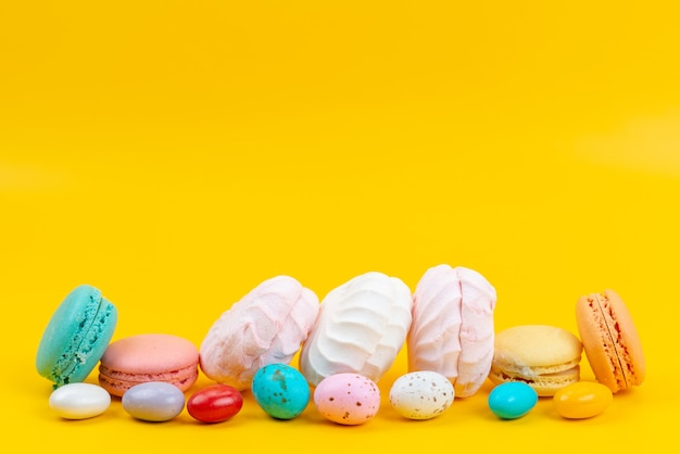 A front view meringues and macarons delicious and sweet on yellow, color rainbow candy