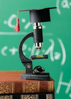 Vista frontale del microscopio sulla pila di libri con cappuccio accademico
