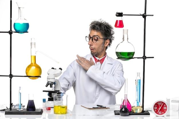 彼のスーツを掃除するソリューションと一緒に座っている白い医療スーツを着た中年の化学者の正面図