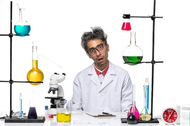 Вид спереди химика средних лет в белом медицинском костюме, сидящего с растворами