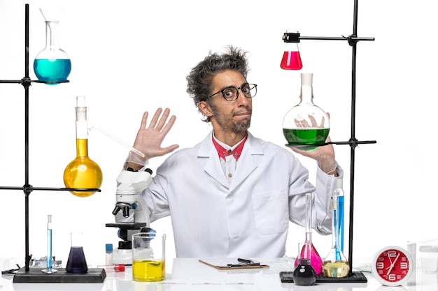 솔루션과 함께 앉아 흰색 의료 소송에서 전면보기 중년 화학자