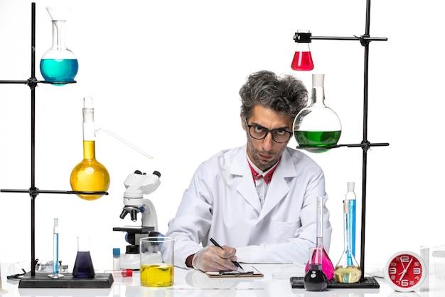 Химик средних лет в белом медицинском костюме, вид спереди, пишет заметки