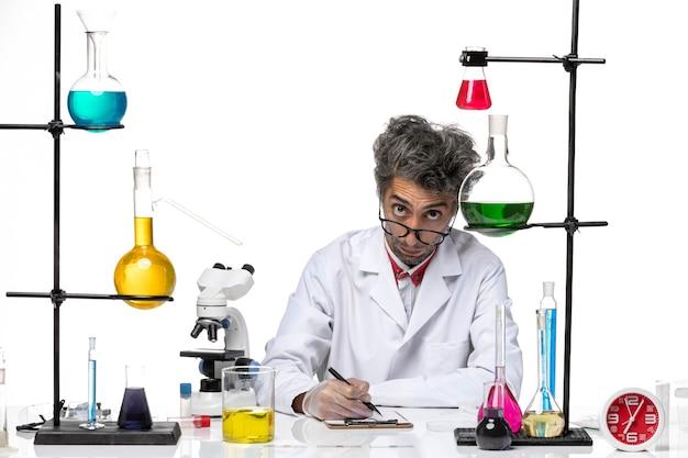 메모를 작성하는 흰색 의료 소송에서 전면보기 중년 화학자