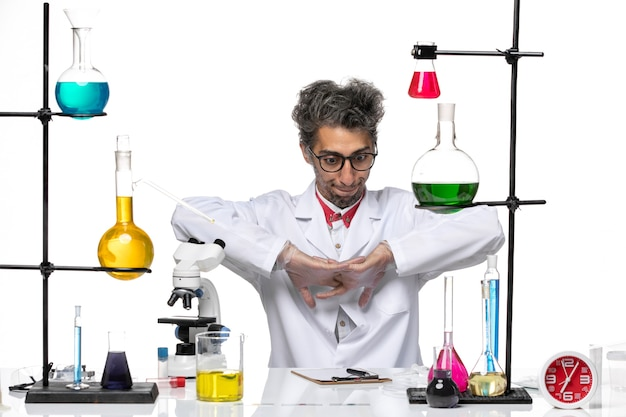 Front view middle-aged chemist in white medical suit preparing for work