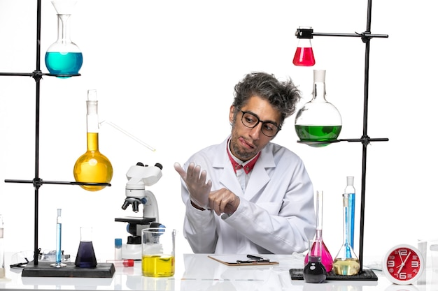 Front view middle-aged chemist in white medical suit sitting with solutions