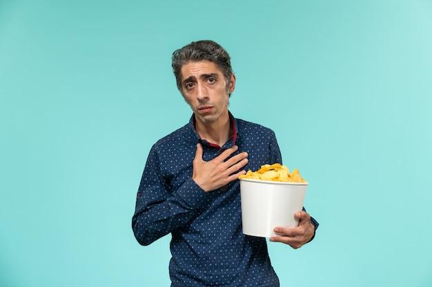 Vista frontale maschio di mezza età che mangia cips sullo scrittorio blu