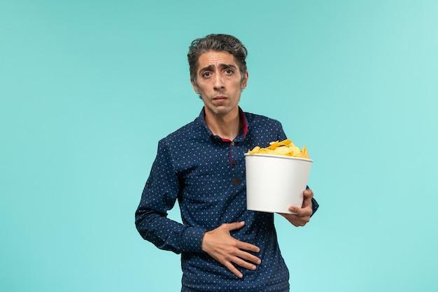 青い表面にcipsを食べる中年男性の正面図